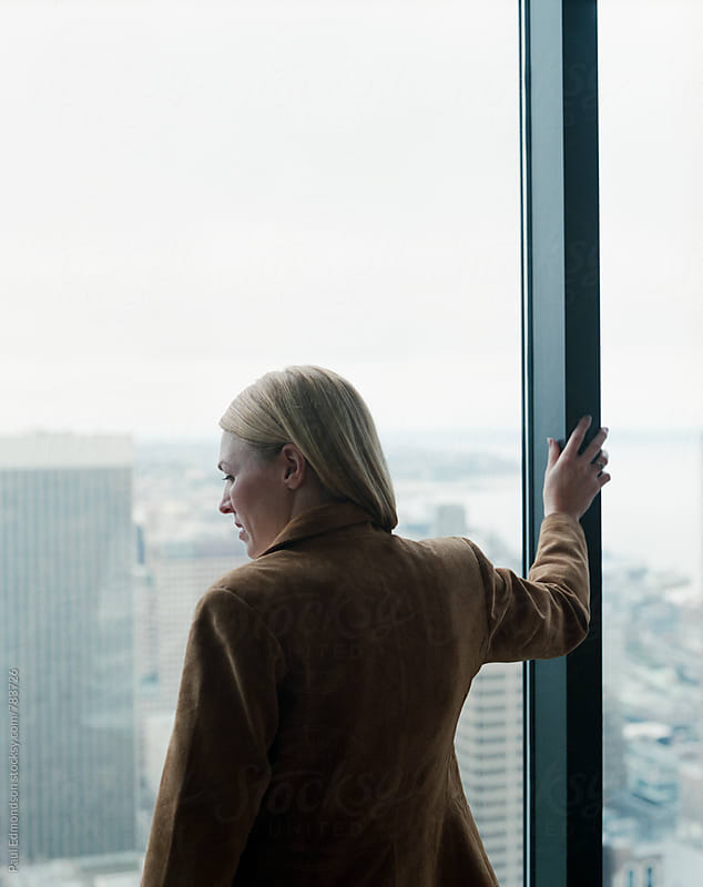 Female executive looking out large office window towards city by Paul Edmondson for Stocksy United