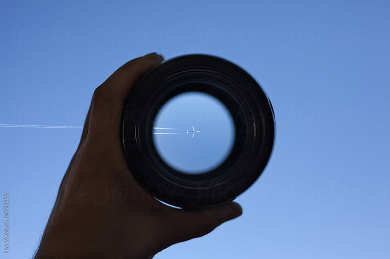 View through spyglass lens to the airplane flying in the sky by Ilya for Stocksy United