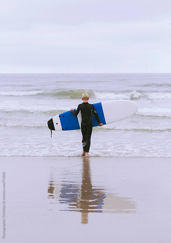 Young boy surfing by Photographer Christian B for Stocksy United