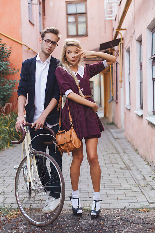 Young fashion vintage couple posing on the street with bicycle by Viktor Solomin for Stocksy United