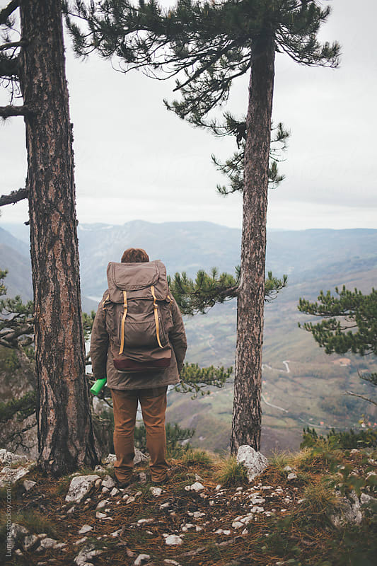 Man With a Backpack Standing on the Edge of a Mountain  by Lumina for Stocksy United