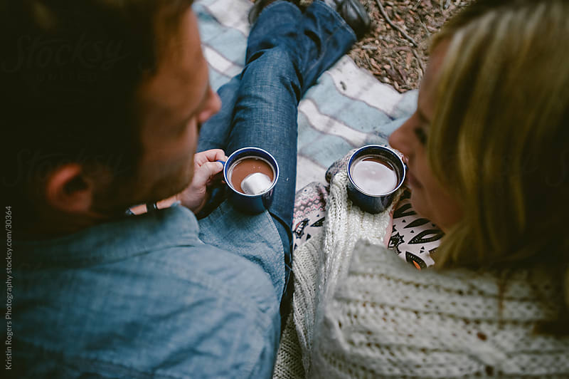 Couple on camping date drinking hot chocolate by Kristin Rogers Photography for Stocksy United