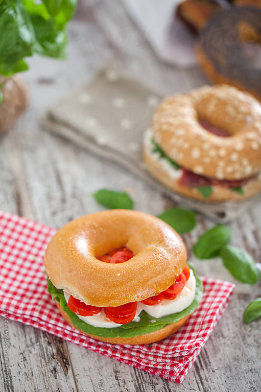 Bagel with Tomato, salad and mozzarella by Davide Illini for Stocksy United