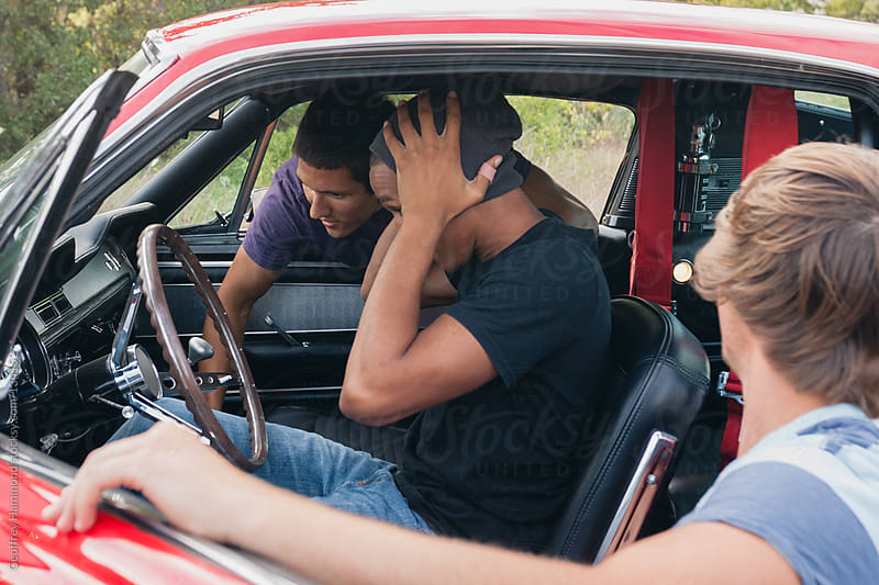 Three young men examine the interior of a classic car by Geoffrey Hammond for Stocksy United