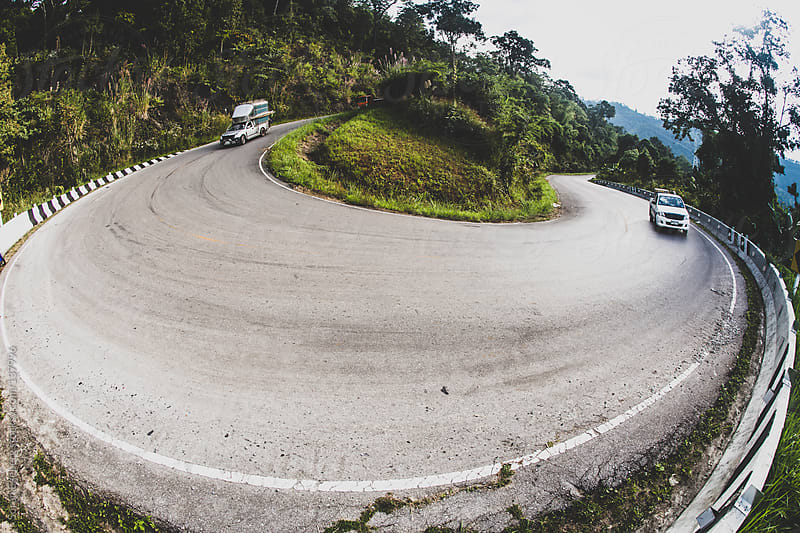 Curvy mountain road bend with cars approaching switchback. by Soren Egeberg for Stocksy United