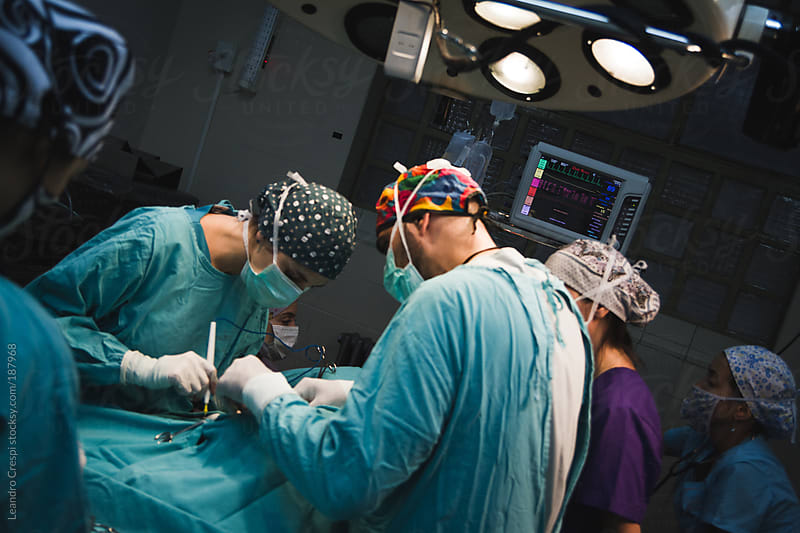 Medical team performing surgery by Leandro Crespi for Stocksy United