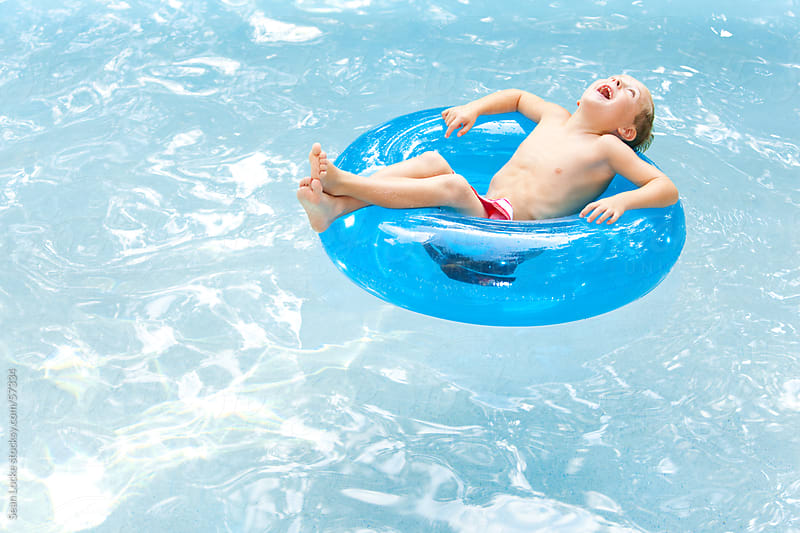 Swimming: Laughing Boy Floating in Tube by Sean Locke for Stocksy United