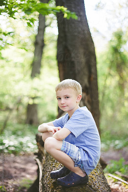 Boy crouches down on log in woods by Amanda Worrall for Stocksy United