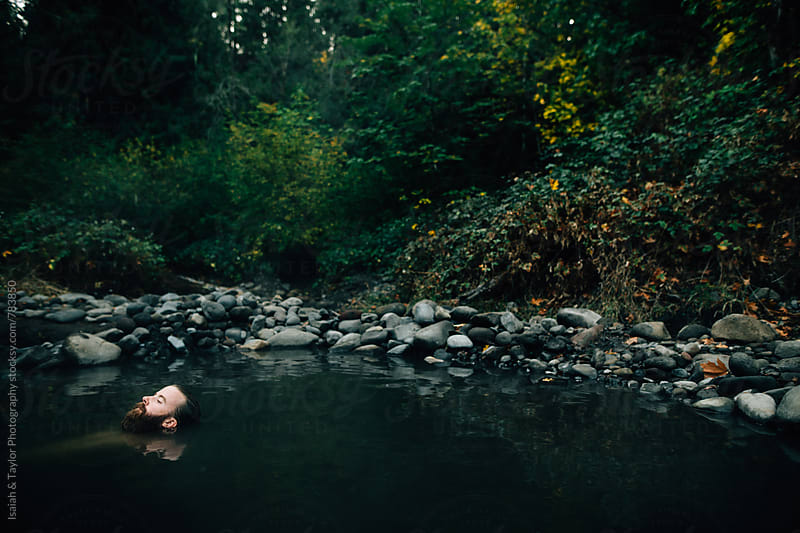 Man floating in water by Isaiah & Taylor Photography for Stocksy United