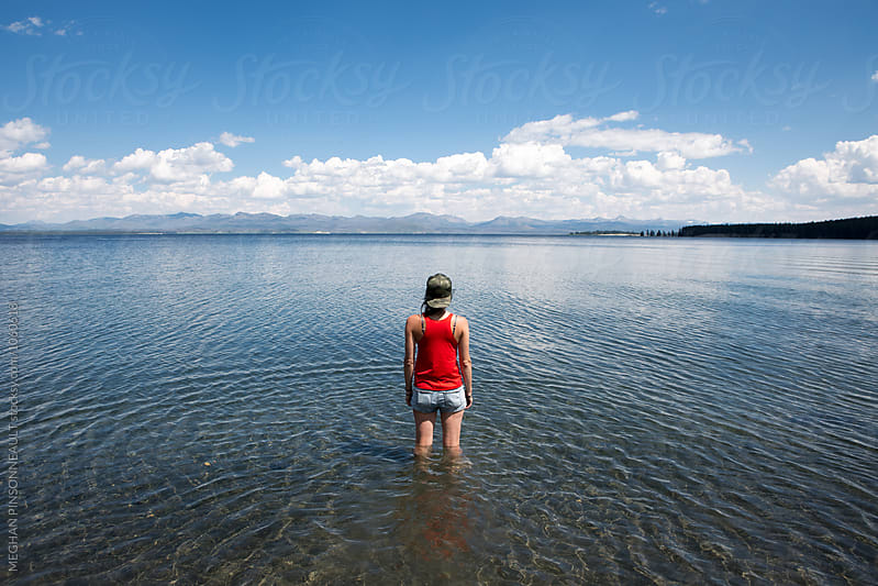 Young Woman Standing in Pretty Lake by MEGHAN PINSONNEAULT for Stocksy United