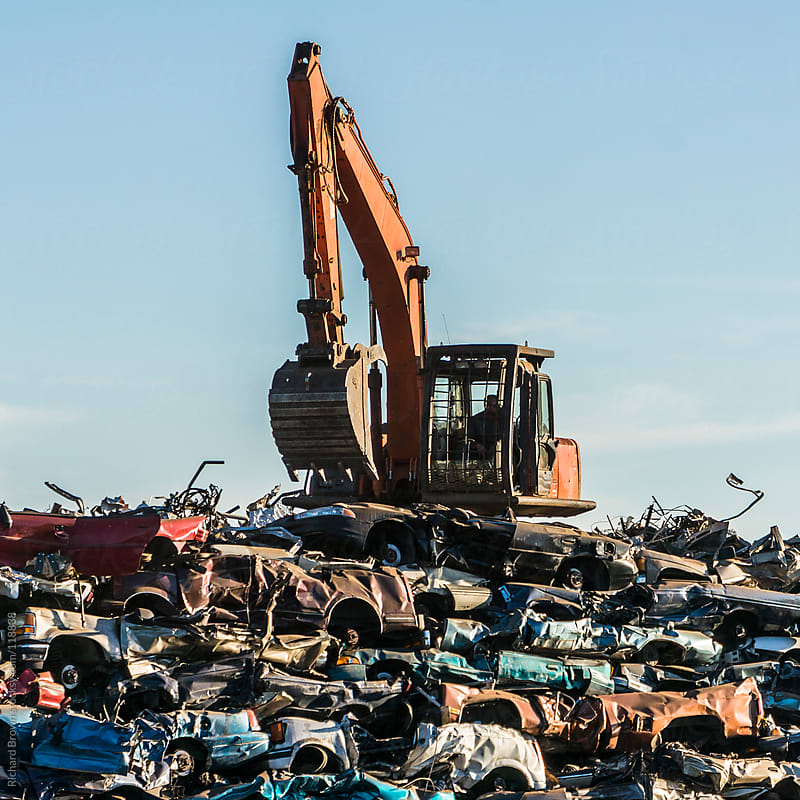 Excavators stacking cars for scrap.  by Richard Brown for Stocksy United