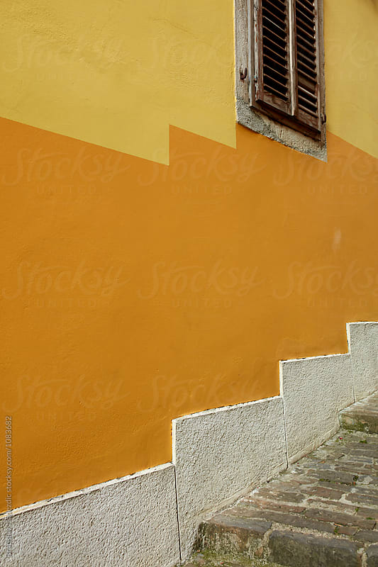 Yellow wall in small seaside village by Bratislav Nadezdic for Stocksy United