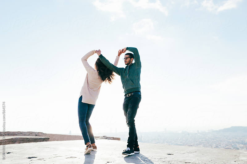 Mixed race couple dancing above city on a sunny day. by BONNINSTUDIO for Stocksy United