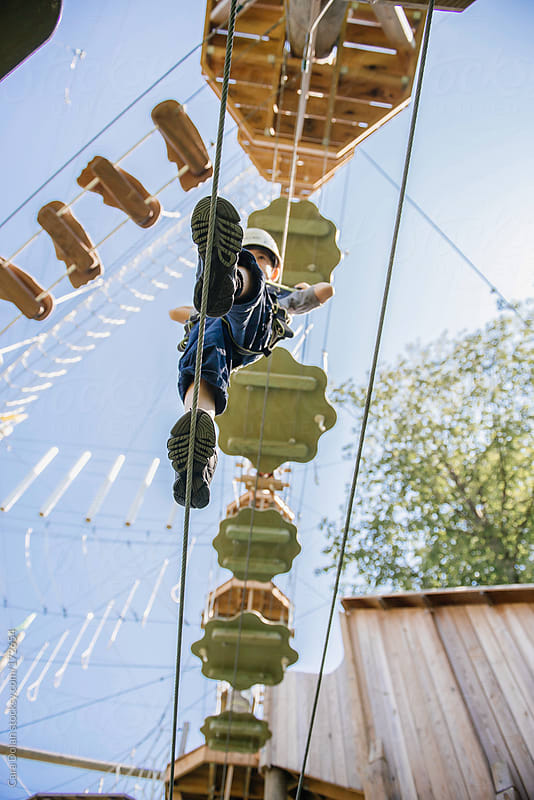 Child traverses a ropes course by Cara Dolan for Stocksy United