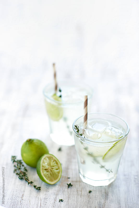 Clear drinks with lime and thyme by Jill Chen for Stocksy United