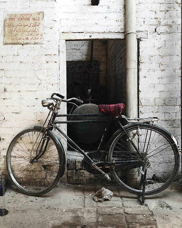 An old bicycle standing against a white wall in a rural area in Pakistan by Murtaza Daud for Stocksy United