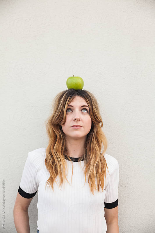 Woman with green apple. by Robert Zaleski for Stocksy United
