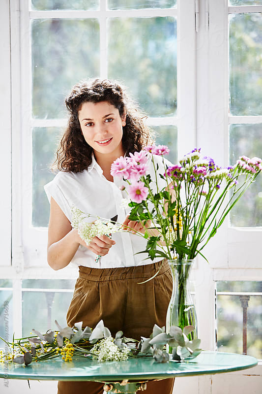 Woman Trimming Flowers In Vase At Home by ALTO IMAGES for Stocksy United
