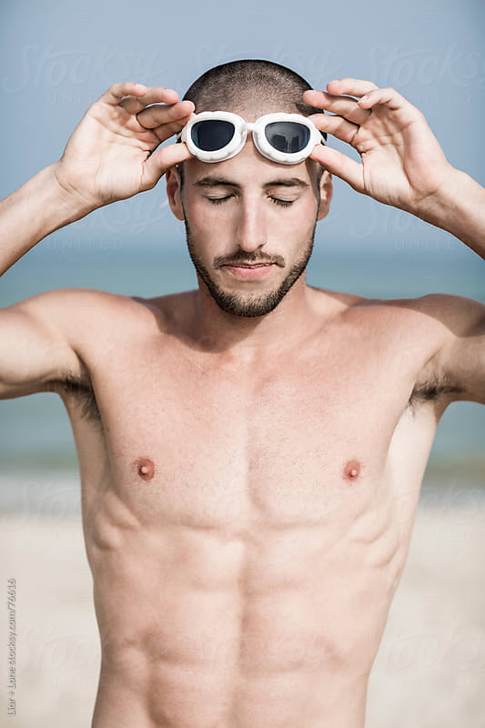 Portrait of swimmer with goggles eyes closed by Lior + Lone for Stocksy United