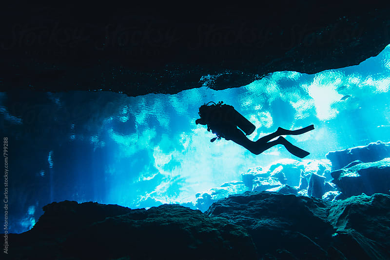 Silhouette of scuba diver doing cave diving in a cenote in Yucatán, Mexico by Alejandro Moreno de Carlos for Stocksy United