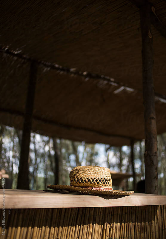 Straw hat in forest bar by Marko Milovanović for Stocksy United