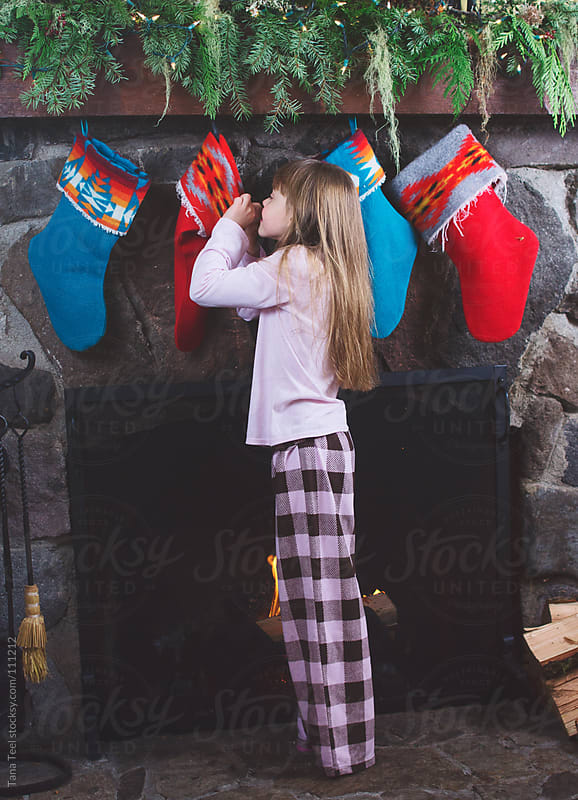 A young girl peeks into her Christmas stocking hanging from the mantle during the holiday by Tana Teel for Stocksy United