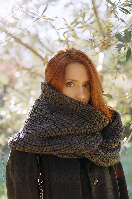 Young woman wrapped in grey scarf by Lyuba Burakova for Stocksy United