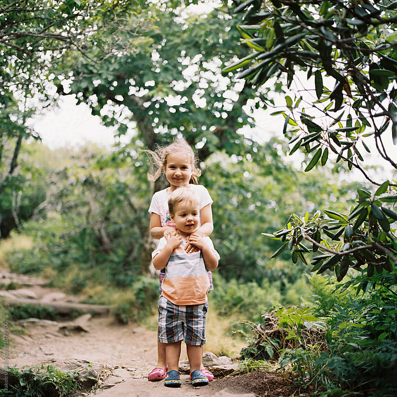 Two young children standing on a hiking trail by Jakob for Stocksy United