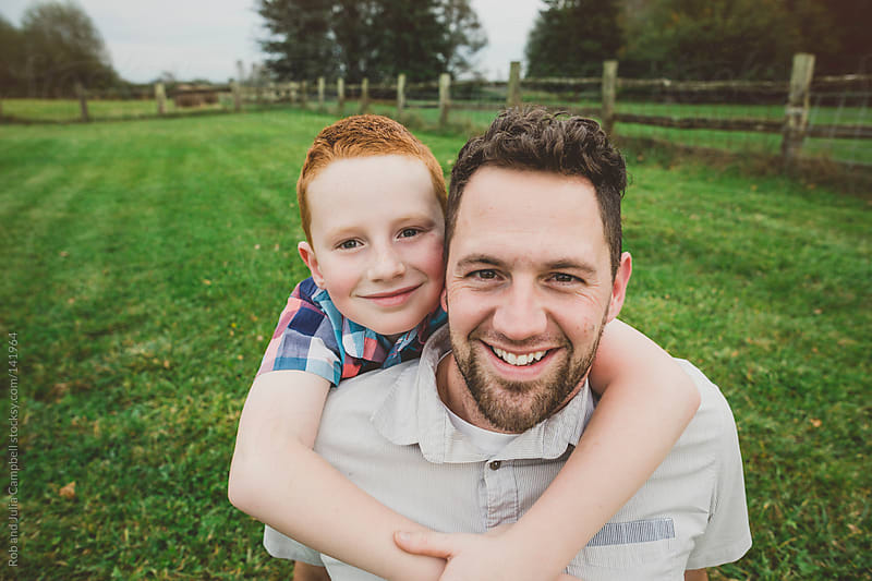 Playful father smiling with young son in farm field by Rob and Julia Campbell for Stocksy United