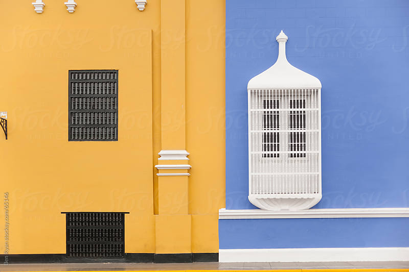 White Spanish colonial balconies on a rendered blue wall and Yellow rendered wall by Ben Ryan for Stocksy United