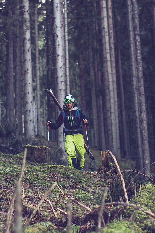 Freerider walking through the forest with his whole skiing equip by Leander Nardin for Stocksy United