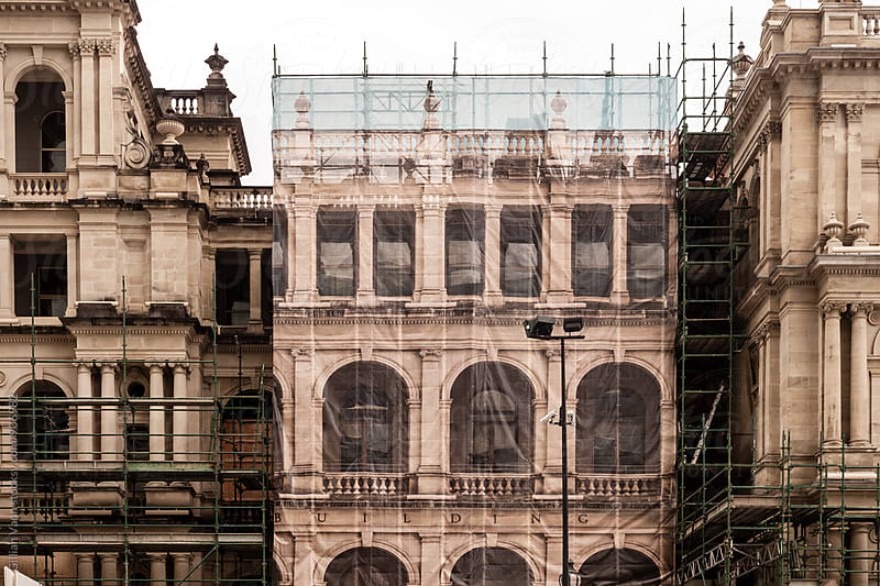 contruction of an old building, with printed scaffold sheeting by Gillian Vann for Stocksy United