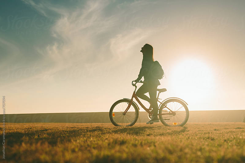 Silhouette of beautiful woman girl riding bicycle on grass lawn at sunset sunrise by Jonathan Caramanus for Stocksy United