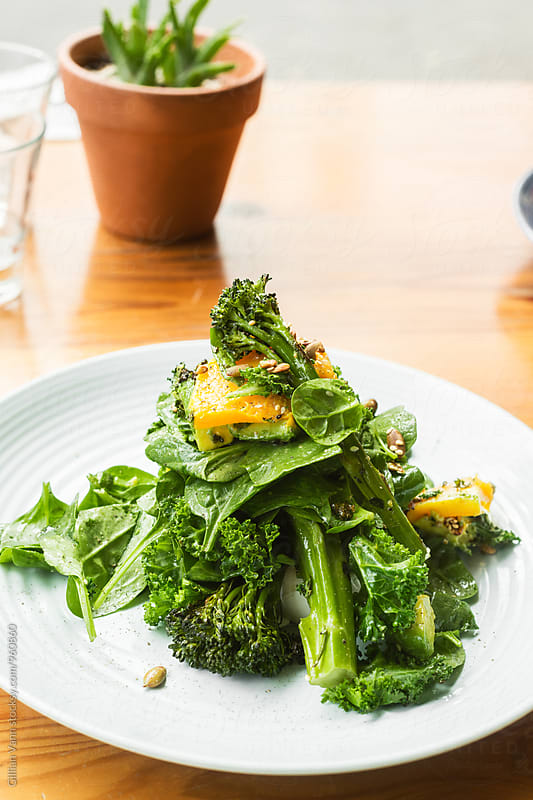 green salad for breakfast, with spinach, broccoli, pumpkin, squash and kale by Gillian Vann for Stocksy United