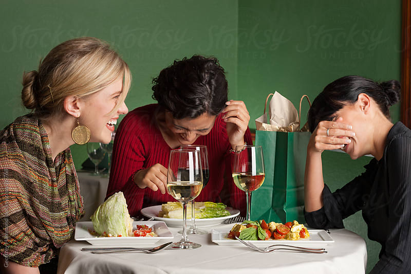 Three Women Laugh Heartily Over Lunch by Geoffrey Hammond for Stocksy United