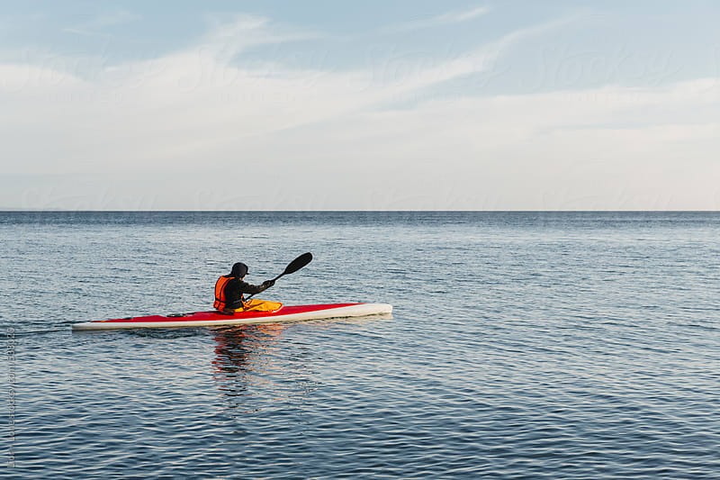 Man sea kayaking in the winter by Lior + Lone for Stocksy United