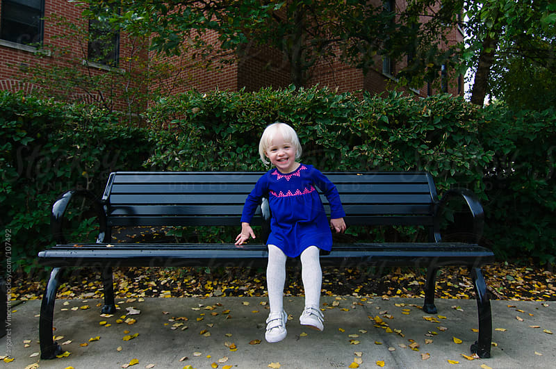 happy little girl on a bench by Margaret Vincent for Stocksy United