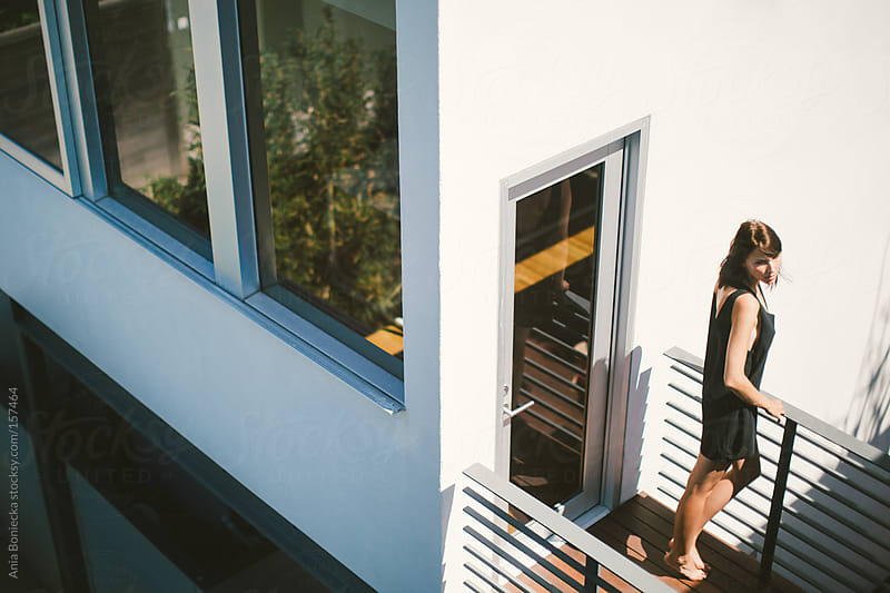 Woman standing on a patio of a modern home by Ania Boniecka for Stocksy United