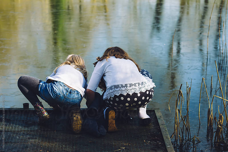 Two little girls pond-dipping by Helen Rushbrook for Stocksy United