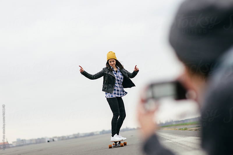 Playful Woman learning to ride Longboard by VegterFoto for Stocksy United