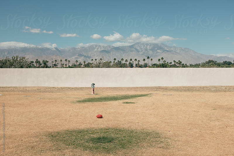 Football lays in an empty field with poor irrigation. by Lucas Saugen for Stocksy United