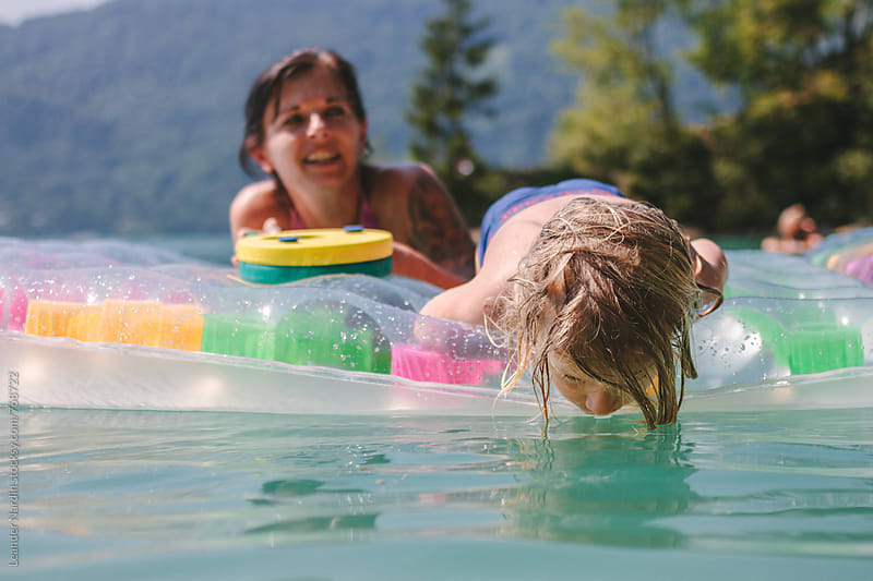 toddler with long blonde hair on an air mattress drinking water from the lake by Leander Nardin for Stocksy United