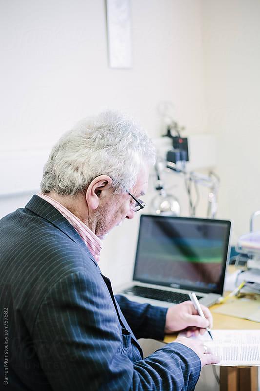 Man working in office. by Darren Muir for Stocksy United
