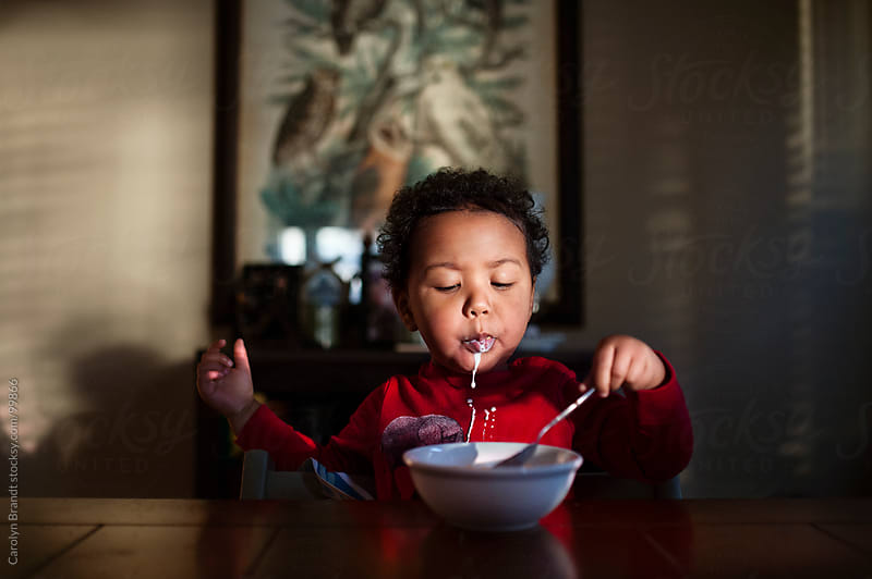 toddler boy eats cereal for breakfast by Carolyn Brandt for Stocksy United