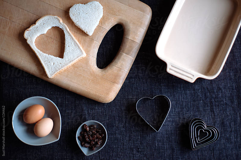 Making a heart shaped bread and butter pudding by Suzi Marshall for Stocksy United