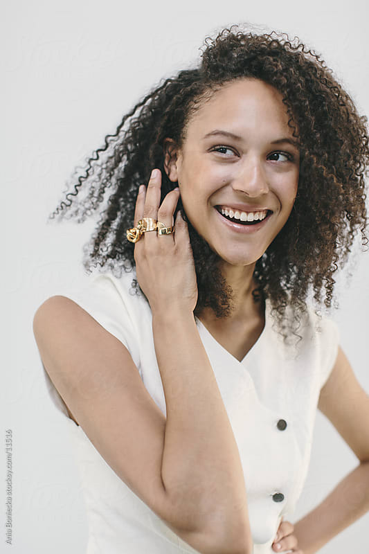 A portrait of a smiling woman touching her hair by Ania Boniecka for Stocksy United