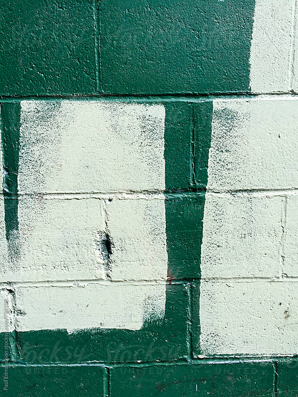 Paint covering graffiti tags on urban wall, close up by Paul Edmondson for Stocksy United