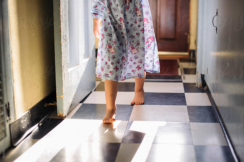 A young girl tip toes barefoot through a kitchen in morning light. by Kelsey Gerhard for Stocksy United