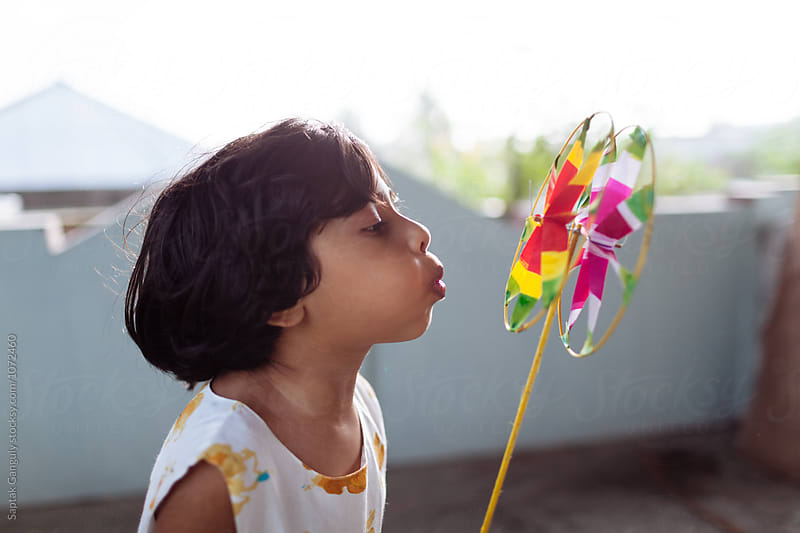 Little girl blowing pinwheel by Saptak Ganguly for Stocksy United