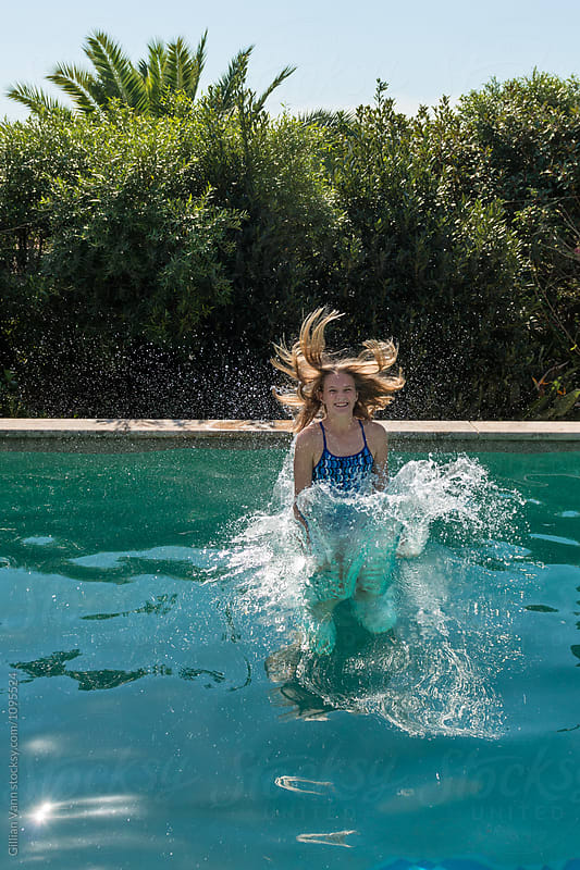 teenage girl jumping into a swimming pool  by Gillian Vann for Stocksy United